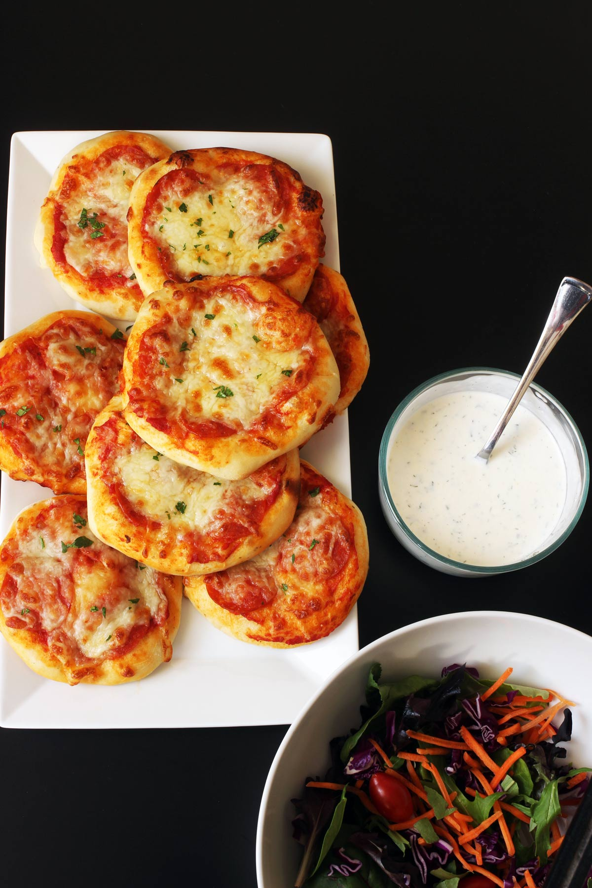 table set with platter of pizzas, bowl of ranch, and large salad