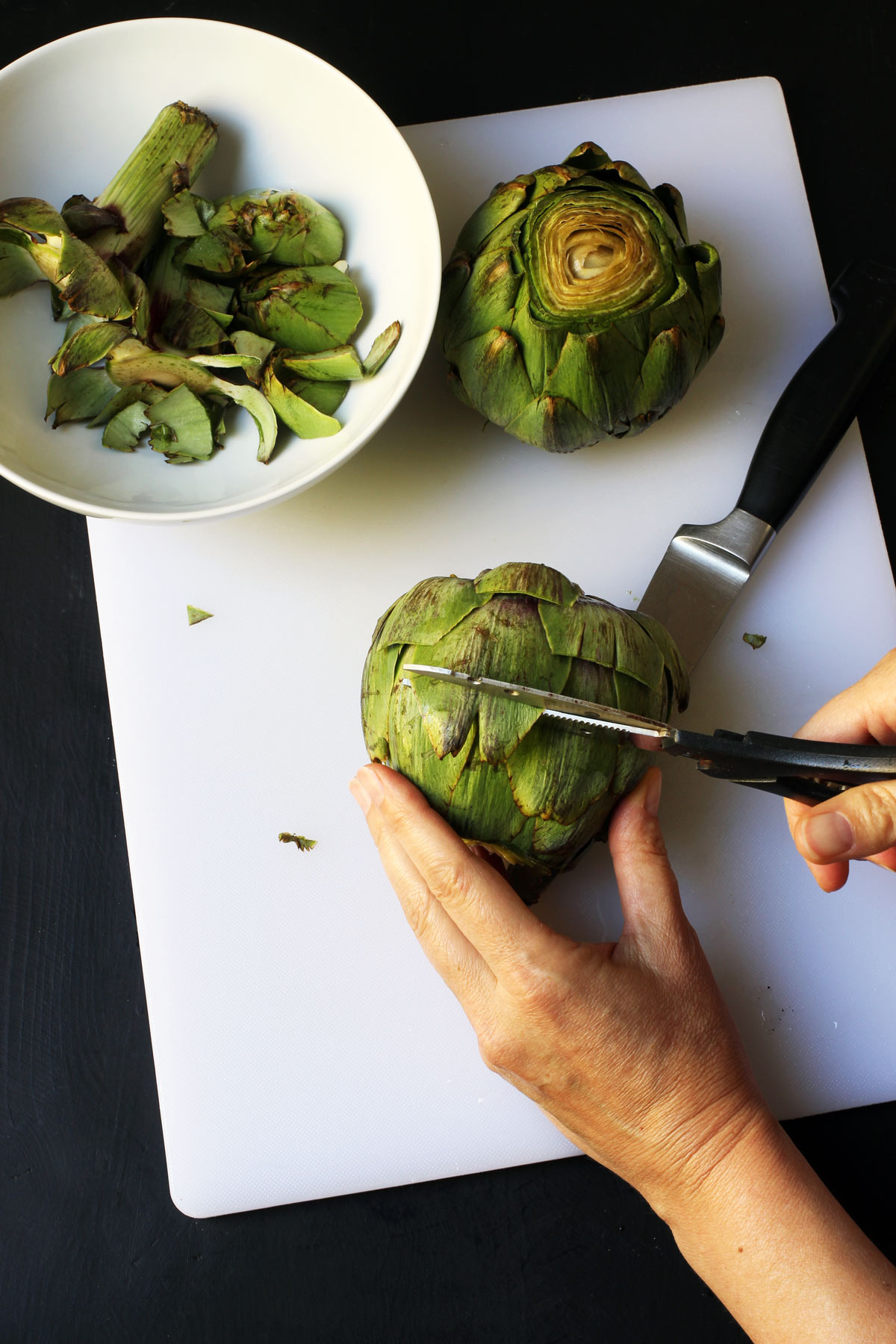 trimming artichoke leaves with scissors