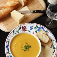 a bowl of soup on a plate with bread and cheese