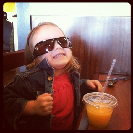 A little girl wearing sunglasses holding a cup at the Broken Yolk Cafe