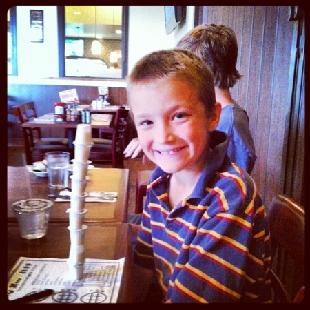 A young boy sitting at a table with a stack of creamers