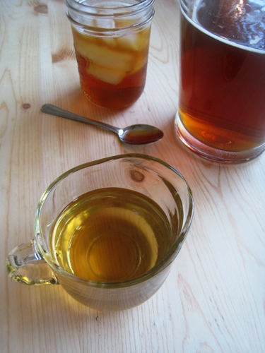 A pitcher of simple syrup next to tea
