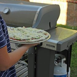 carrying pizza to the grill