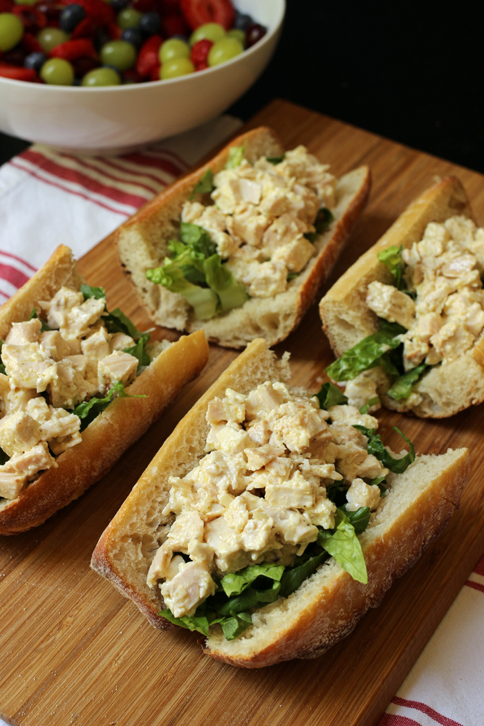 chicken caesar sandwiches on board with fruit