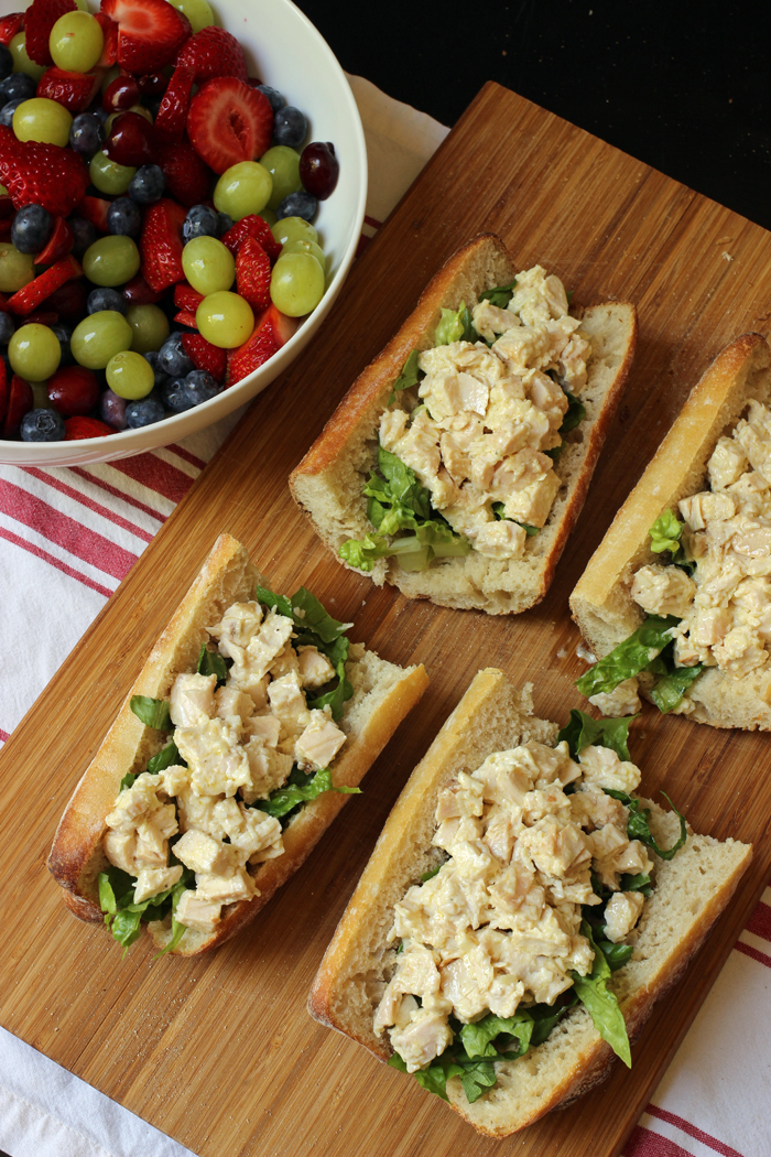 baguette sandwiches with chicken salad and a bowl of fruit