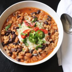 bowl of homemade chili with beans and lots of toppings