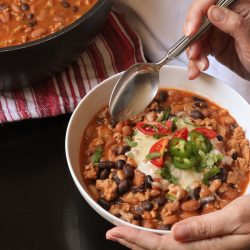 A bowl of chili with toppings