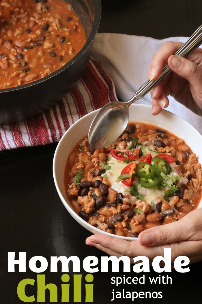 woman's hands holding bowl of chili with toppings