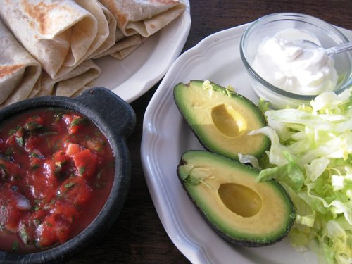 plate of avocados and other burrito toppings