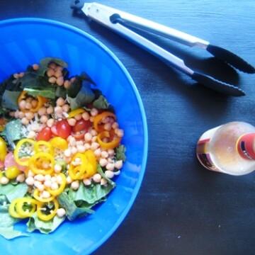 blue bowl of salad with bottle