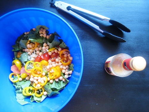 blue bowl of salad with bottle of dressing
