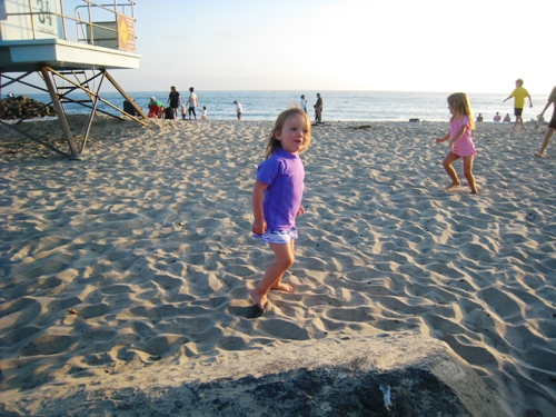 little girls playing on a sandy beach