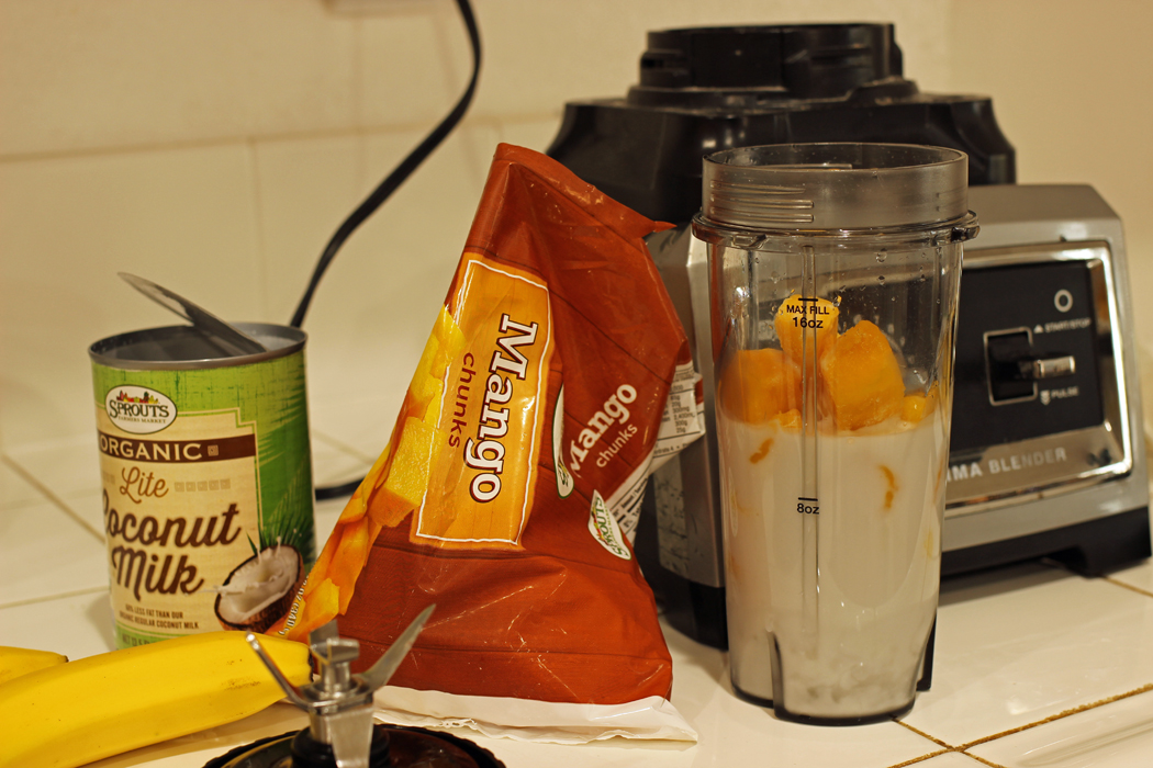 smoothie ingredients on counter, blender, and single serve cup
