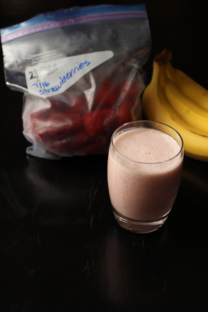 red banana smoothie with strawberries and bunch of bananas
