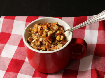 red mug of yogurt oats and nuts on gingham napkin