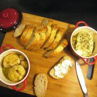 roasted garlic and baked goat cheese on wooden board