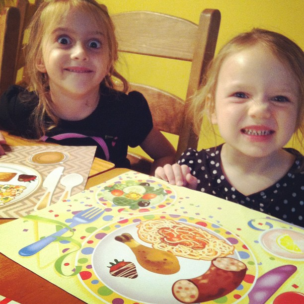 little girls sitting at a table with placemats