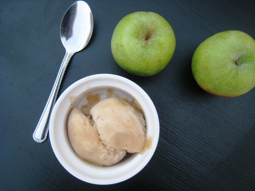 A bowl of Apple Sorbet with spoon and apples