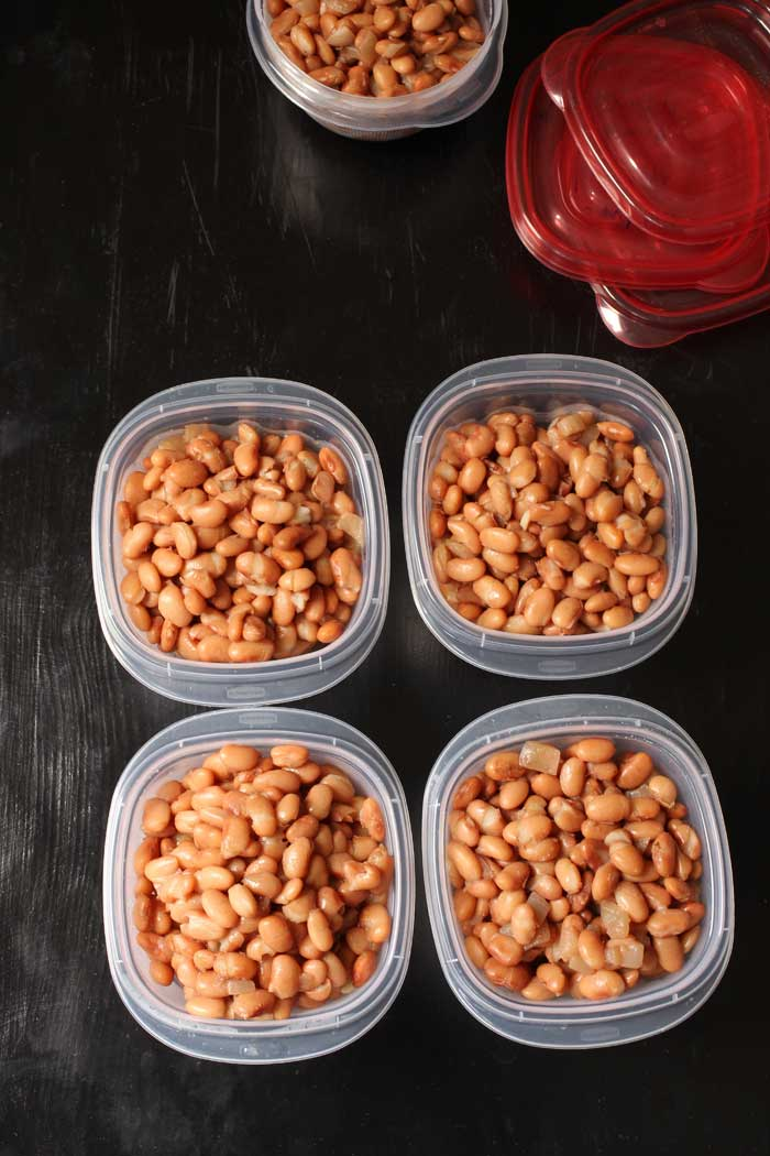 cooked pinto beans divided into containers for freezing