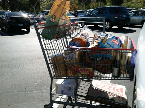 A full shopping cart in a parking lot full of cars