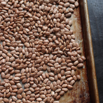 pinto beans being sorted on baking sheet