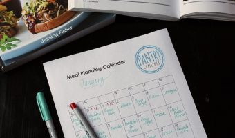 monthly meal planning calendar with pens and cookbooks