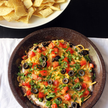 seven layer dip on white cloth with bowl of chips