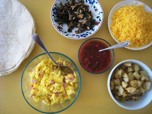Bowls of breakfast burrito bar items laid out