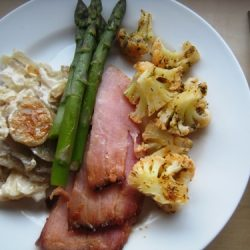 A plate of food, with ham and cauliflower
