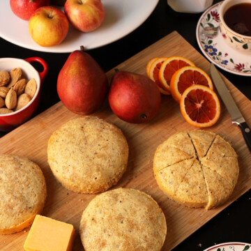tables set with cakes cheese fruit nuts and tea