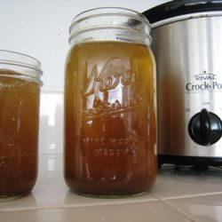 Beef broth in jars next to crockpot