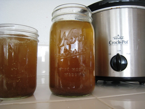 Beef broth in jars on counter, with slow cooker