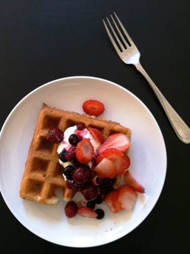 waffles on a plate with cream and berries