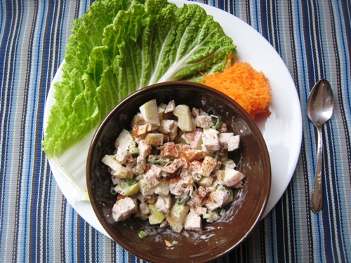 A bowl of chicken salad on a plate, with cabbage wraps