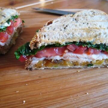 A cut in half sandwich sitting on top of a wooden cutting board