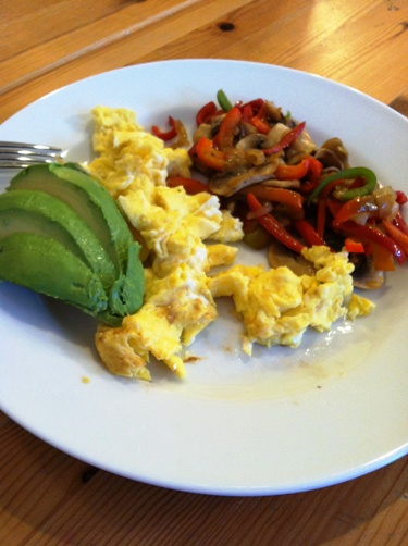 A plate of scrambled eggs with vegetables and avocado