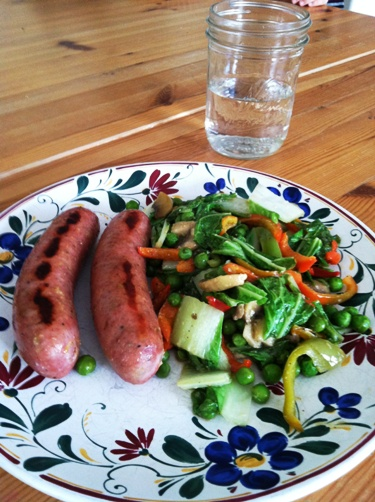 A plate of sausages and vegetables