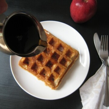 pouring syrup on a waffle on a plate