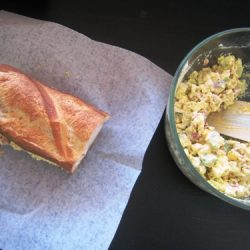 egg salad in a bowl next to sandwich