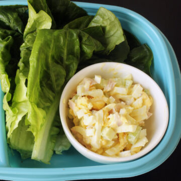 dish of ham and egg salad with lettuce leaves