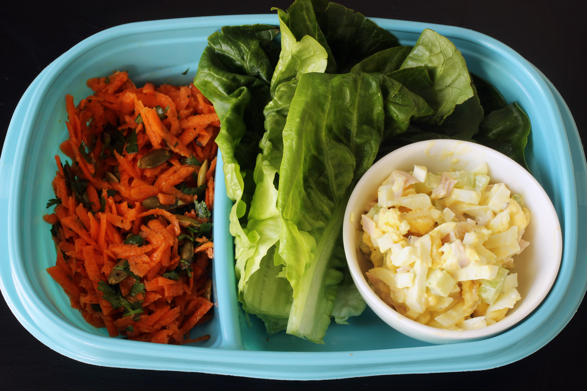 meal prep with carrot salad, lettuce leaves, and dish of egg salad