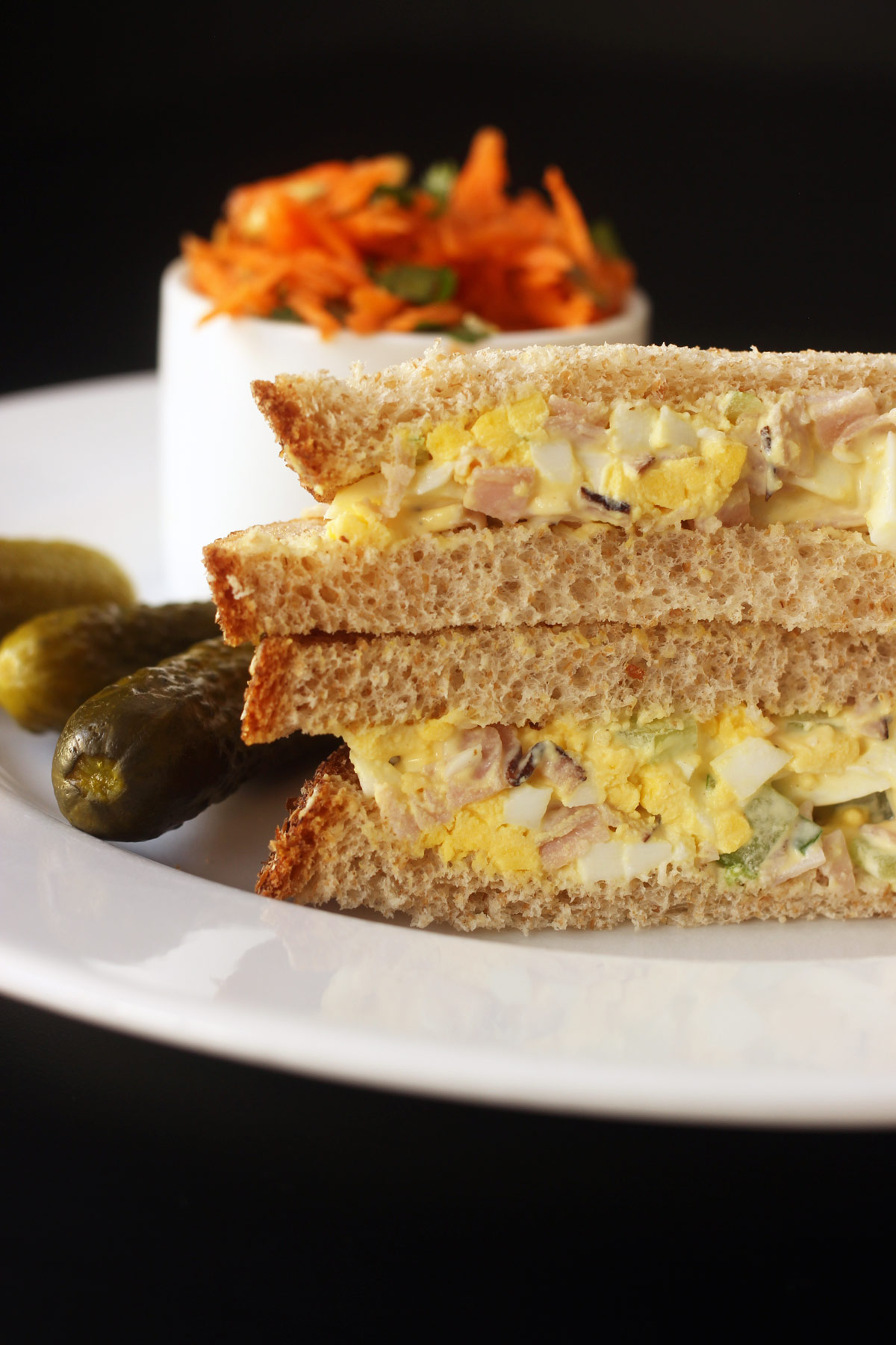 stacked halves of egg salad sandwich on plate with pickle