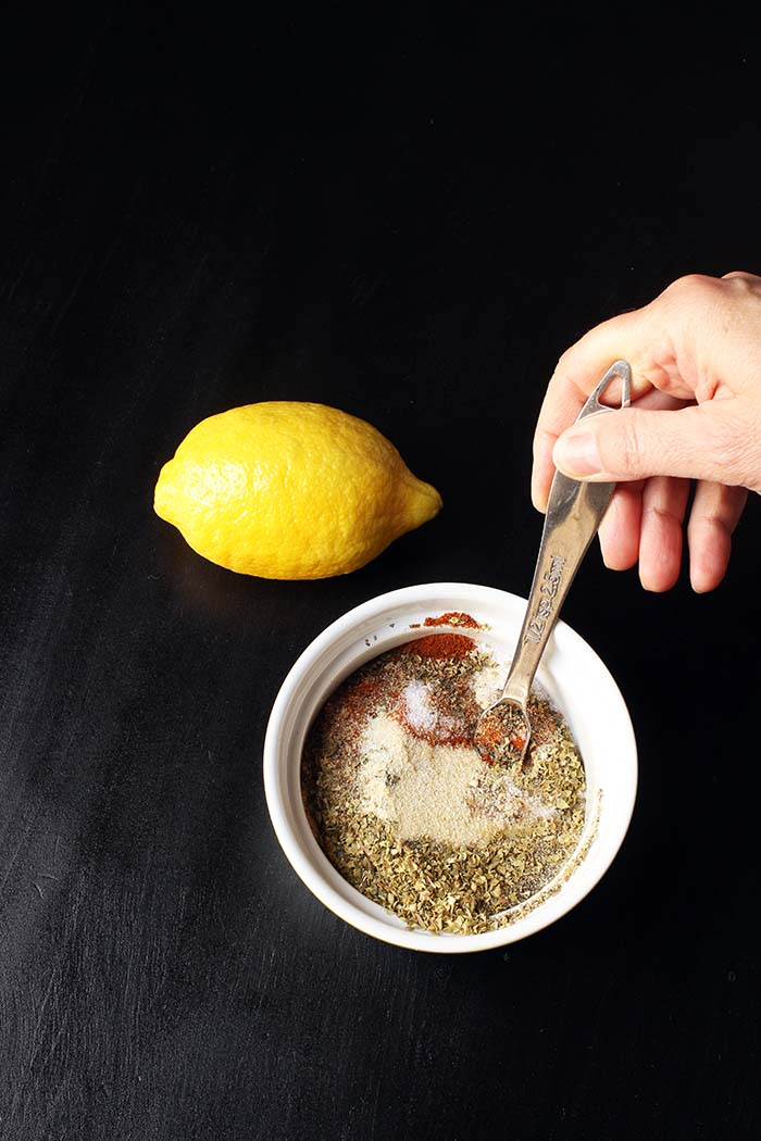 lemon on black table next to hand stirring spice mix