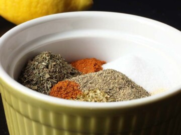 spices in green bowl with lemon in background