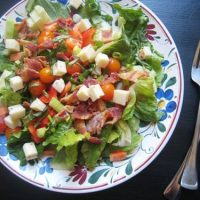 A bowl of salad on a plate, with Bacon
