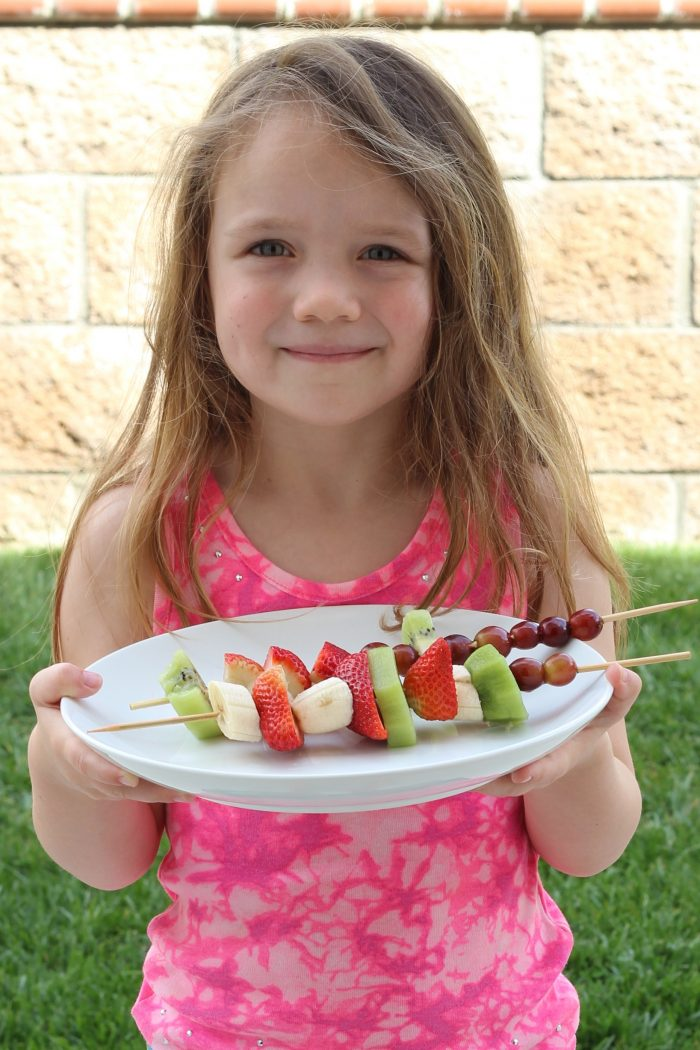 girl holding platter of fruit kabobs
