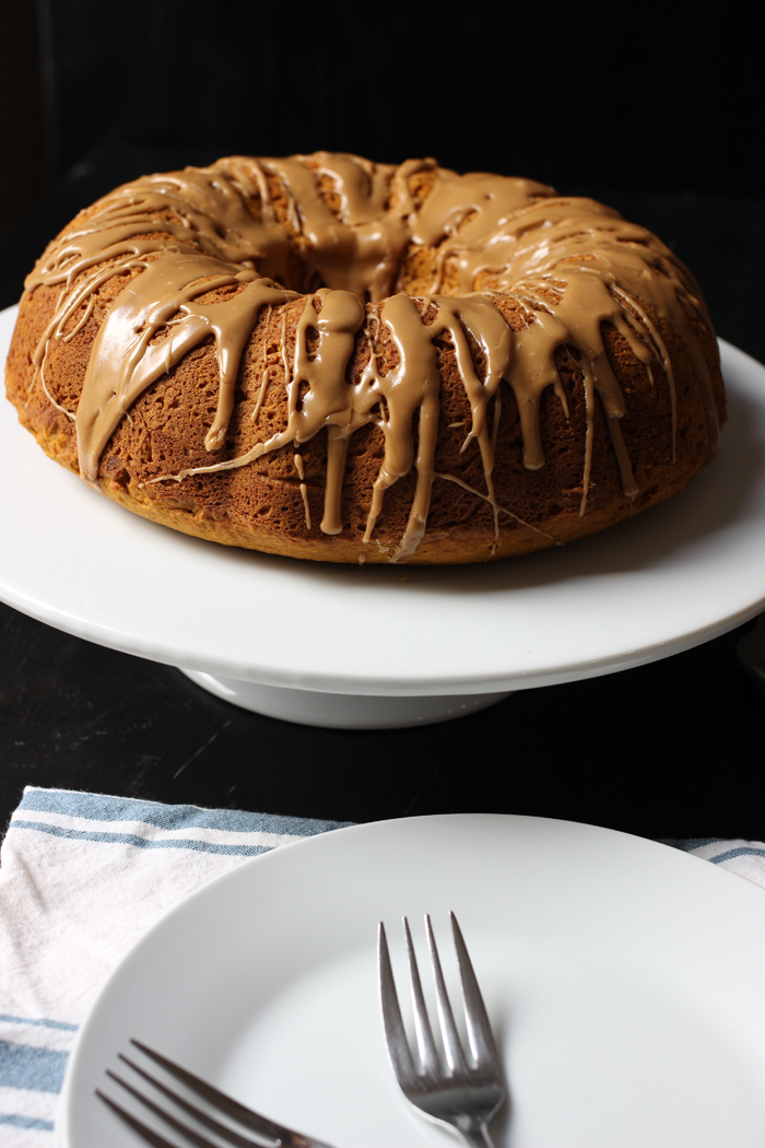 Pumpkin Bundt Cake with Maple Glaze on cake stand with plates and forks