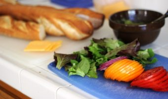 A close up of a cutting board with sliced sandwich fixings