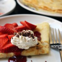 close up of crepe folded and topped with strawberries and cream