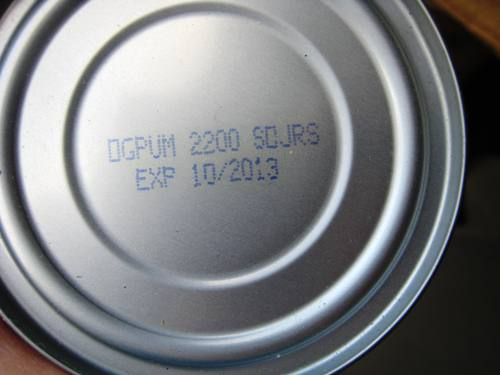 A close up of can stamped with an expiration date